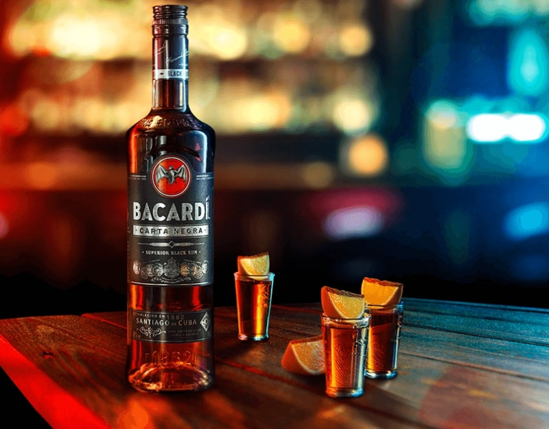 bacardi black bottle on table with shot glasses