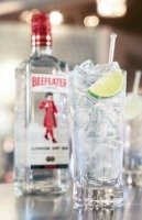 Beefeater gin bottle and gin and tonic cocktail in a high glass with ice and lemon slice