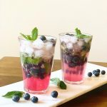 blueberry mojito in 2 glasses with blueberries spread around them