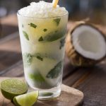 Coconut Mojito with lime wedges and half a coconut in background