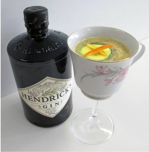 hendricks gin bottle with gold rush cocktail in a fancy tea glass