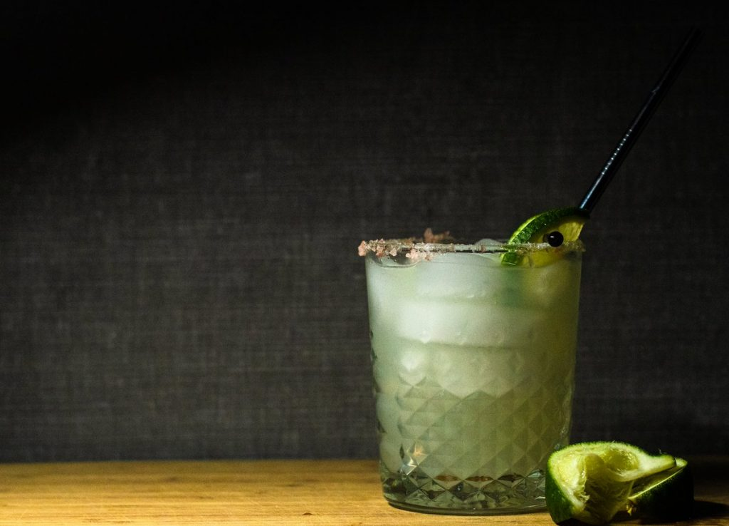 jalapeno margarita on the table with spent lime shell