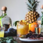 pineapple margarita in a glass with tequila and pineapple standing beside