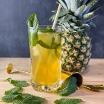 pineapple mojito in a glass with mint leaves and a pineapple around it