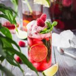 raspberry mojito in a glass garnished with raspberry mint and lime wedge