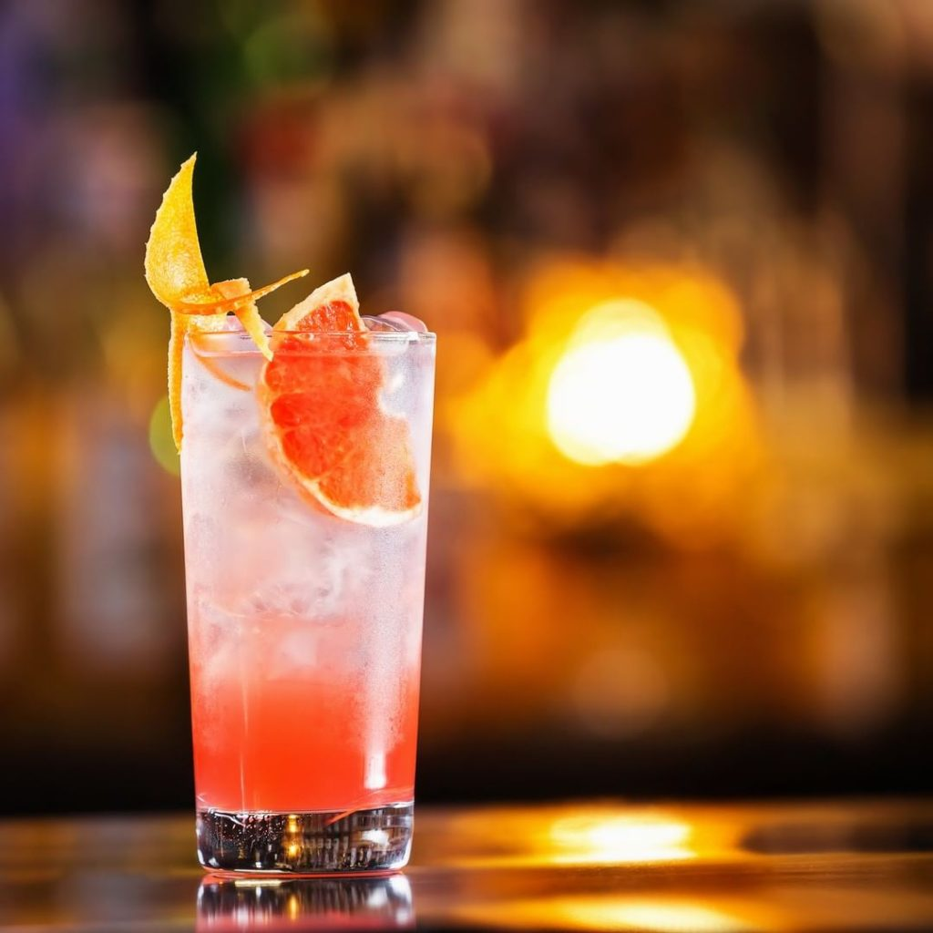 rosemary greyhound cocktail in a glass with grapefruit slice as garnish