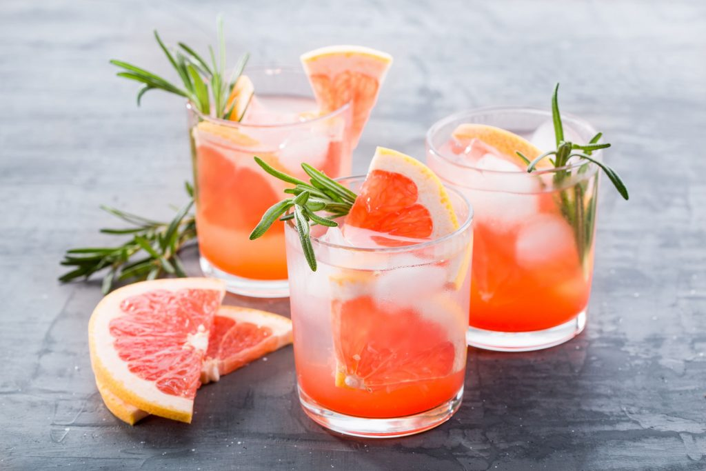 rosemary greyhound cocktail in 3 glasses with grapefruit slices as garnish