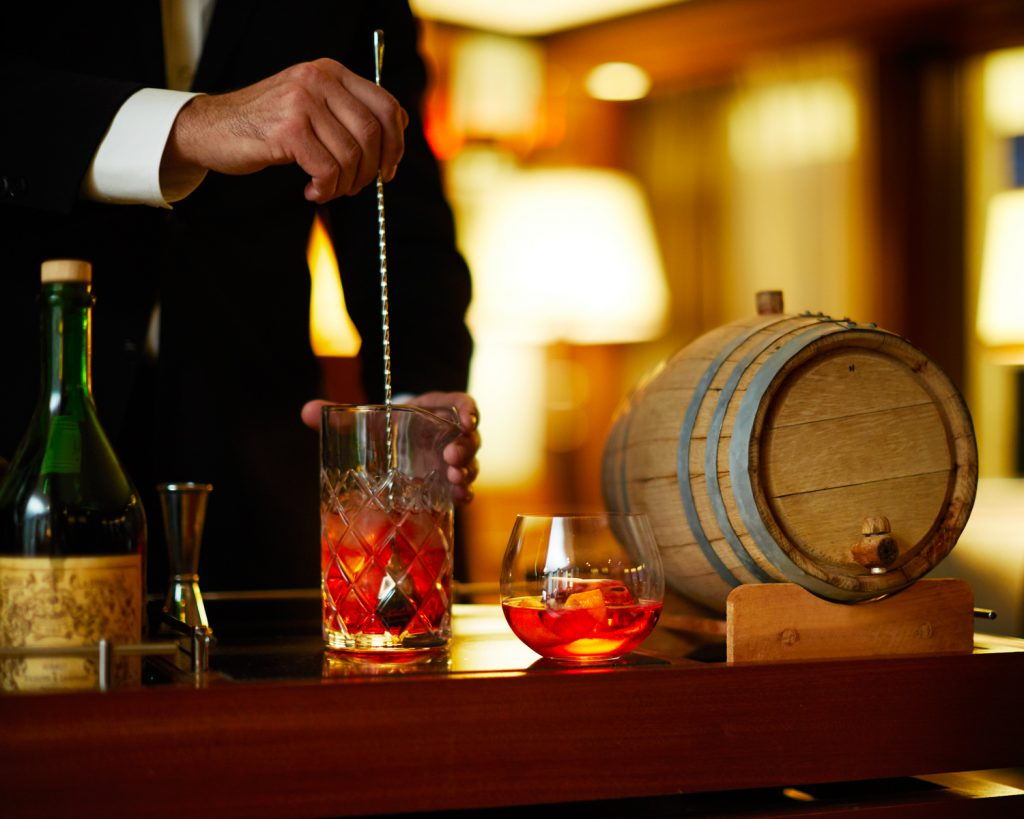 negroni cocktail being stirred on a bar top
