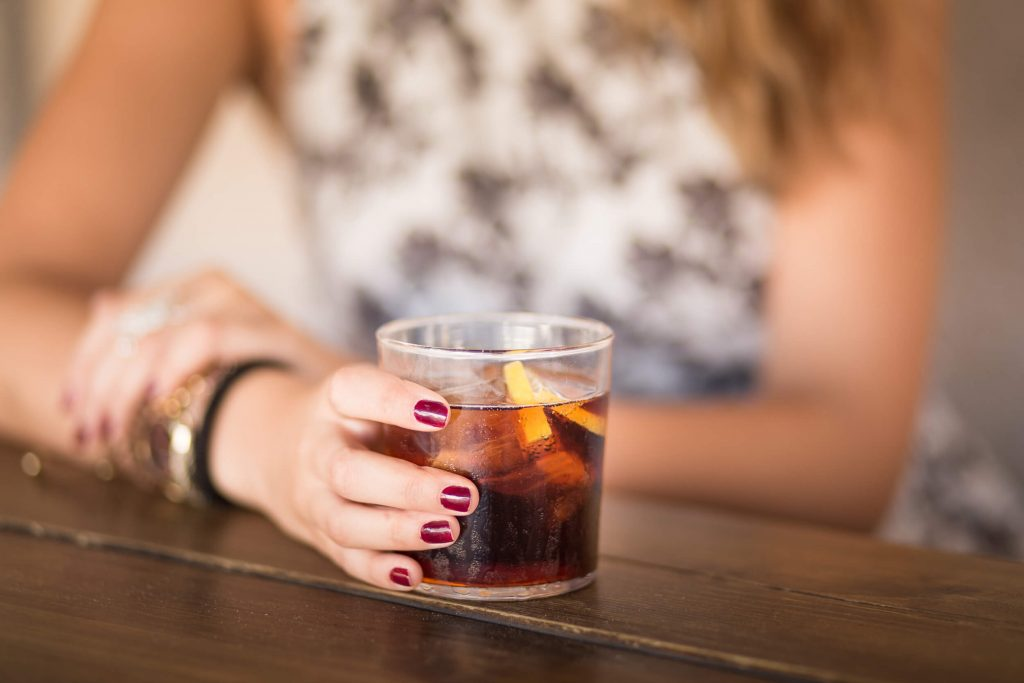 woman drinking cuba libre cocktail on a table